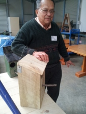 Ern Bently with one of the birdhouses made by the Men's Shed