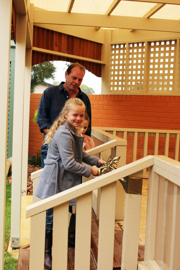 Family members Evie, Rosie and James Thompson cut the ribbon to open the new sand play structure in memory of Jane Rapp.