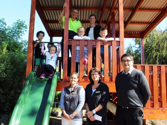 Mercia Lowe (Parent Committee, Chair); Scott Whicker (Kimberly Clark, Millicent Mill Manager); Paul Duka (Wattle Range Council, Director Corporate Services), Sarah Murby and Clara Walker (Centre Co‐Directors) and children admire the new structure.